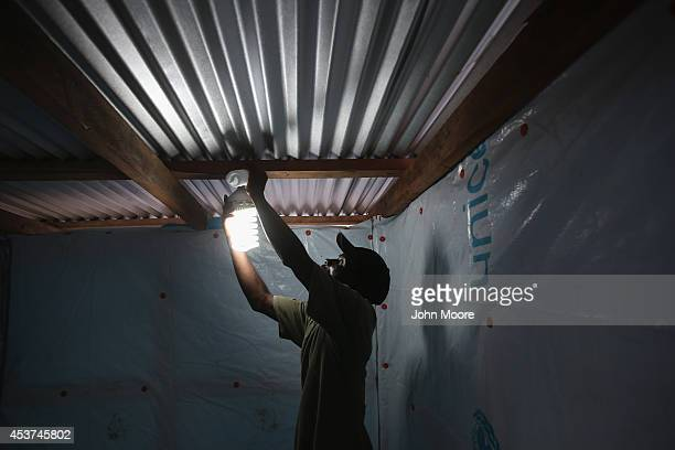 An electrician illuminates a shower in the new Doctors Without Borders Ebola treatment center on August 17 2014 near Monrovia Liberia The facility...