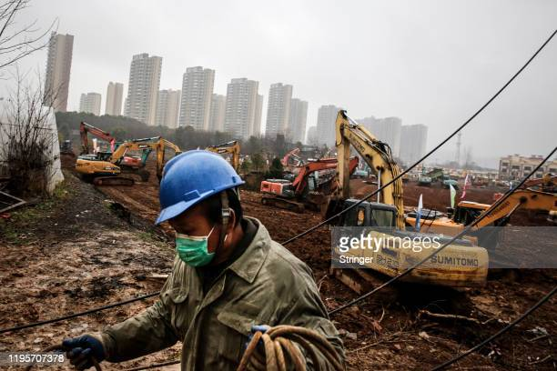 An electrician sets up wiring while construction workers drive excavators at the site of a new 1000bed field hospital being built to accommodate the...