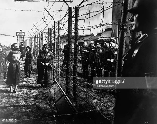 An electrified barbed-wire fence separates male and female prisoners at a German concentration camp. A Nazi guard keeps watch in the foreground. The...
