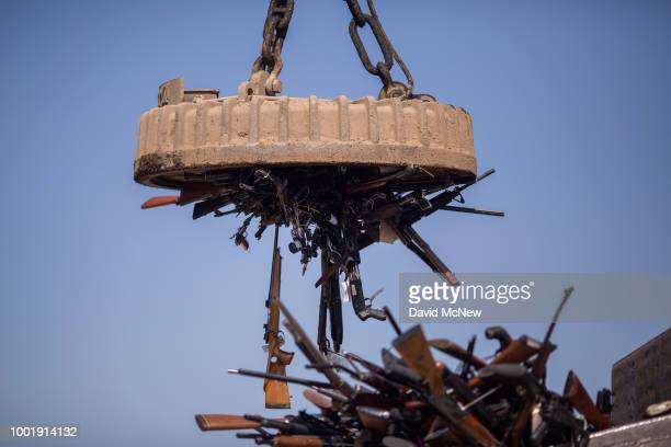 An electromagnet is used to pick up some of approximately 3500 confiscated guns to be melted down at Gerdau Steel Mill on July 19 2018 in Rancho...