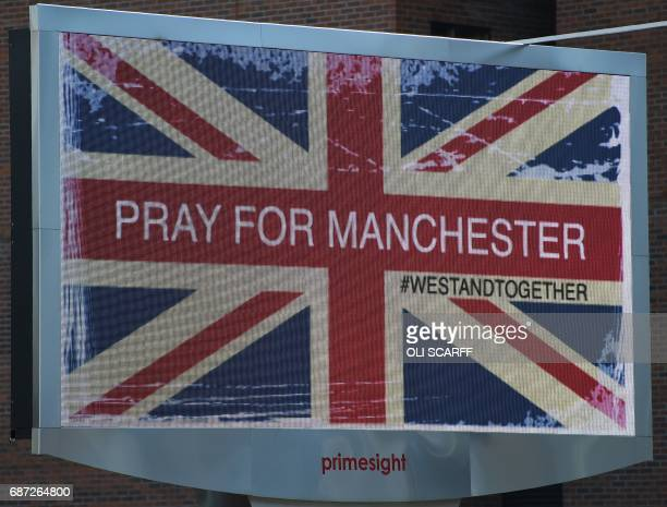 An electronic advertising board displays a Union flag and the words 'Pray For Manchester' close to the Manchester Arena in Manchester northwest...