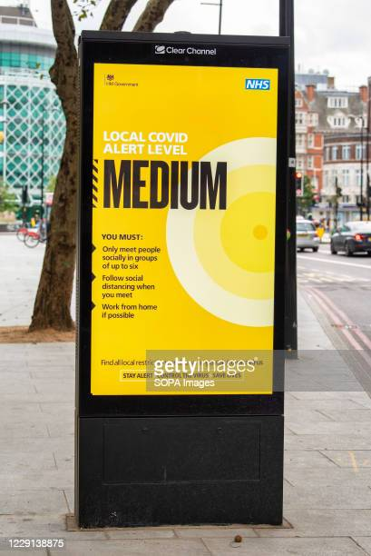 An electronic advertising screen in the borough of Camden, London showing the local Covid19 alert level is on Medium under the Governments new...