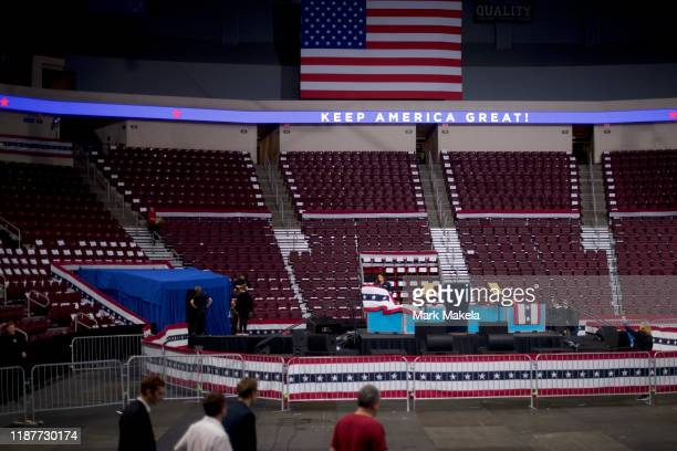 """An electronic banner states """"KEEP AMERICA GREAT"""" while below a member of production staff drapes a patriotic banner on the stage before President..."""