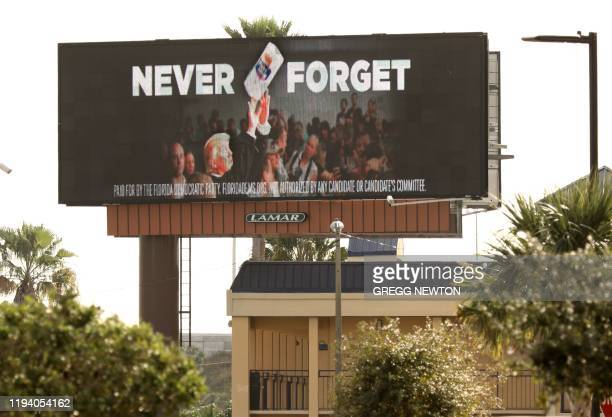An electronic billboard advertisement paid for by the Florida Democratic Party reading Never Forget and showing US President Donald Trump throwing a...