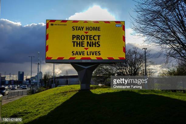 An electronic billboard sign emits Covid-19 safety information to the public on February 10, 2021 in Manchester, England. Health authorities are...