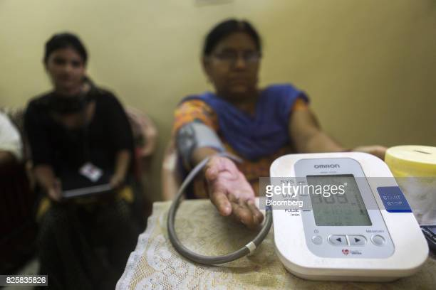 An electronic blood pressure machine takes a patient's readings during a free doortodoor screening program conducted by Public Health Foundation of...