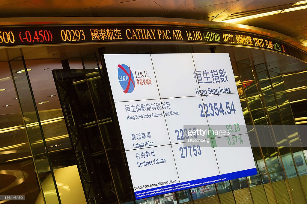 An electronic board displays the Hang Seng Index figure on the trading floor of the Hong Kong Stock Exchange in Hong Kong, China, on Tuesday, Aug. 13, 2013. Hong Kong Exchanges & Clearing Ltd., operator of the Hong Kong Stock Exchange, is scheduled to release second-quarter results tomorrow. Photographer: Jerome Favre/Bloomberg via Getty Images