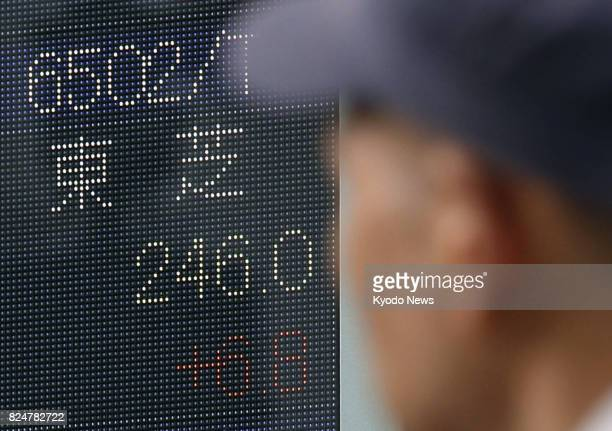 An electronic board in Tokyo shows the share price of Toshiba closing at 24600 yen up 680 yen on July 31 its last day on the Tokyo Stock Exchange's...