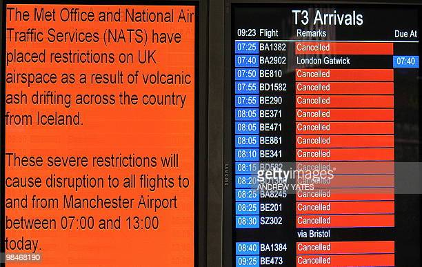 An electronic board showing the cancellation of inbound flights is pictured beside a notice warning of disruptions at an arrival terminal in...