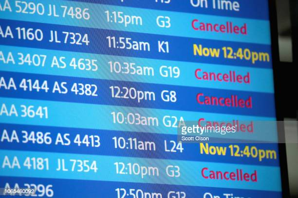 An electronic board shows flight delays and cancellations at O'Hare International Airport after an early winter snowstorm left more than 7 inches of...