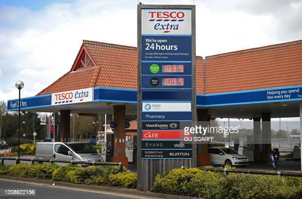 An electronic display board shows the prince in pence per litre for petrol and diesel at a Tesco supermarket store in York, northern England on March...