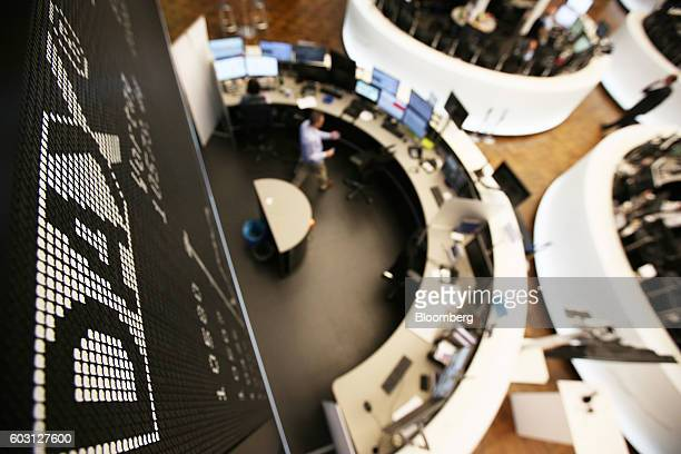 An electronic display board sits above traders' desks inside the Frankfurt Stock Exchange in Frankfurt Germany on Monday Sept 12 2016 EON SE cut most...