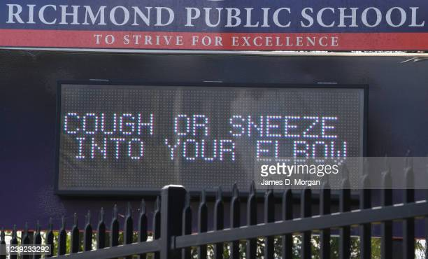 An electronic display sign asking children to cough or sneeze into their elbows for hygiene purposes outside Richmond Public School on June 01 2020...