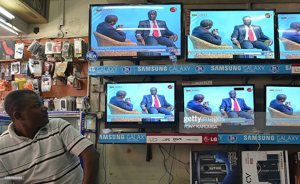 An electronic goods trader follows a televised debate on charges faced by Kenyan President Uhuru Kenyatta at the Hague-based International Criminal Court (ICC) being dropped, on television sets displayed in an electronics shop on December 5, 2014 in the Kenyan capital Nairobi. The ICC's Chief prosecutor Fatou Bensouda, dropped crimes against humanity charges against the president dealing a blow to the tribunal after a long-running and troubled case. AFP PHOTO/Tony KARUMBA