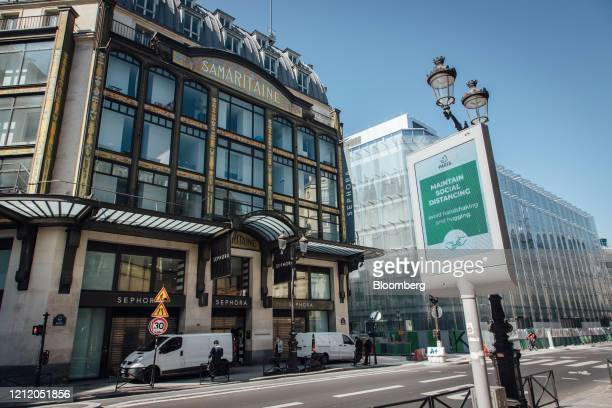 An electronic information screen advises the public of social distancing measures outside the Samaritaine luxury department store building operated...