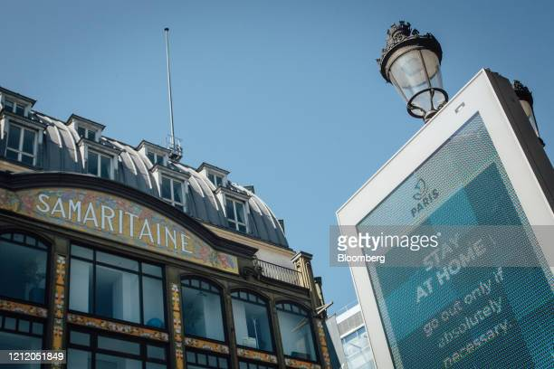 An electronic information screen advises the public to 'stay at home' outside the Samaritaine luxury department store building operated by LVMH Moet...