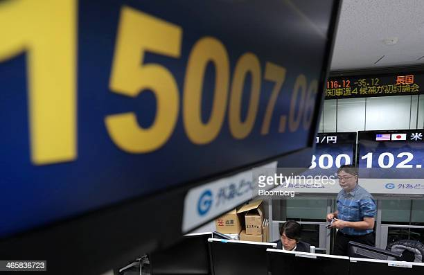 An electronic monitor flashes the closing price of the Nikkei 225 Stock Average at a foreign exchange brokerage in Tokyo Japan on Thursday Jan 30...
