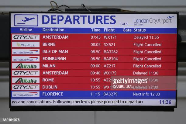 An electronic passenger information display board shows delayed or cancelled flights inside London City Airport in east London on January 23 2017 A...