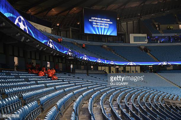 An electronic screen displays a message in German saying 'due to adverse weather conditions todays match was cancelled' inside the Etihad stadium in...