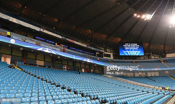 An electronic screen displays a message saying 'due to adverse weather conditions todays match has been postponed' inside the Etihad stadium in...