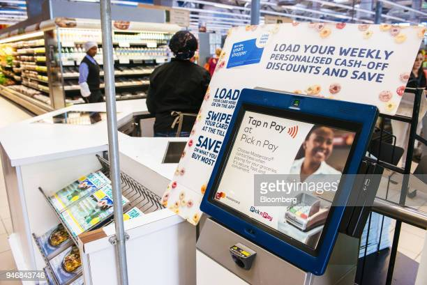 An electronic screen displays information regarding contacless payment at the check out area inside a Pick n Pay Stores Ltd supermarket in...