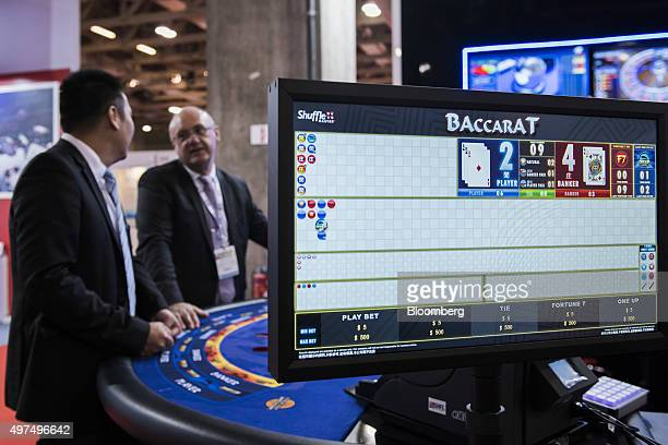 An electronic screen stands at a baccarat table at the Macao Gaming Show in Macau China on Tuesday Nov 17 2015 The show runs until Nov 19...