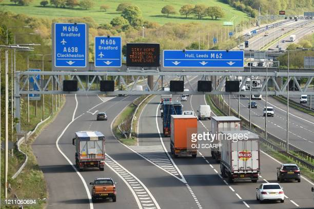 An electronic sign urges people to stay home and make essential journeys on the M62 motorway near Bradford, in northern England, on April 27, 2020 as...