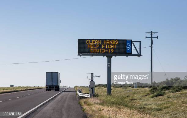 """An electronic sign warning people to """"Clean Hands Help Fight Covid-19"""" is located on Highway 46 near the start of California's """"Petroleum Highway""""..."""
