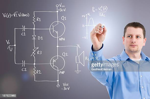 An electronics engineer drawing a circuit on glass wall