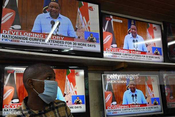 An electronics shop assistant watches on television Kenya's President Uhuru Kenyatta giving a state of the nation address on the coronavirus pandemic...