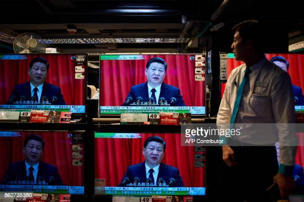 An electronics shop employee in Hong Kong on October 18, 2017 looks at television sets showing a news report on China's President Xi Jinping's speech...