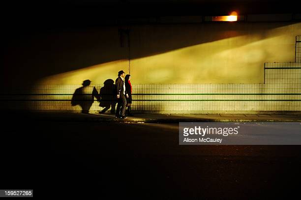 An elegant couple, holding hands, walk through an urban underpass. They are walking into the golden light.