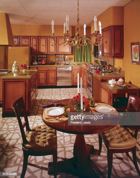 An elegant kitchen with attached dining area features a chandelier plenty of counter and cabinet space an oven and stove a fully stocked pair of...