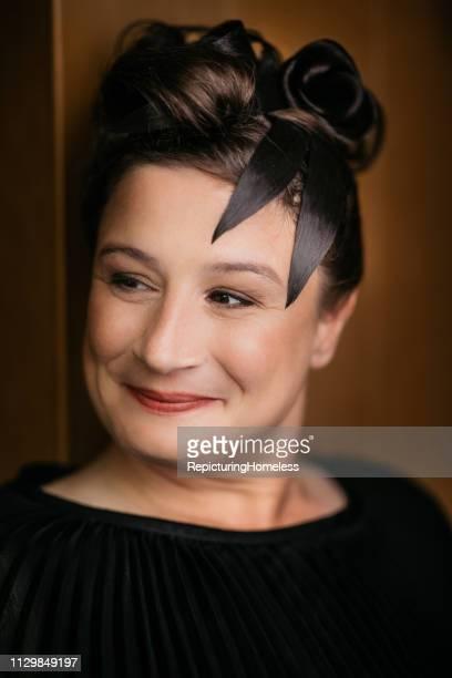 Eine elegante Dame schaut mit einem Lächeln zur Seite.