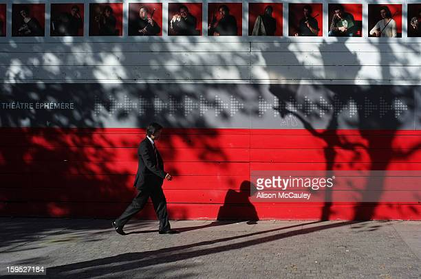 An elegant man in a dark suit walks past la Comedie Française in Paris. The wall is a striking crimson and the shadows on the wall are dramatic.