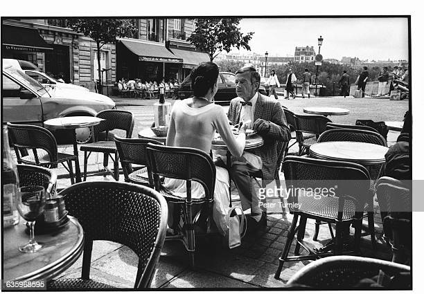 An elegant Parisian couple share intimate conversation while dining al fresco at the Brasserie de l'Ile Saint Louis