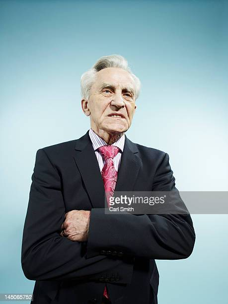 An elegant senior man with his arms crossed looking displeased