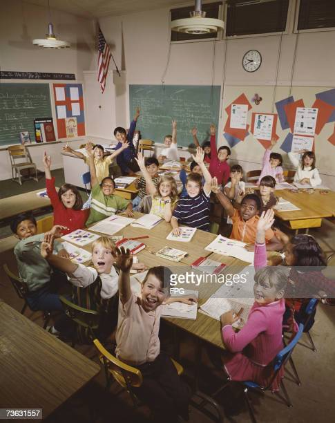 An elementary school classroom full of children eagerly raising their hands to volunteer or answer a question, circa 1965.