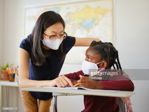 an elementary school student and teacher in a classroom - teacher stock pictures, royalty-free photos & images