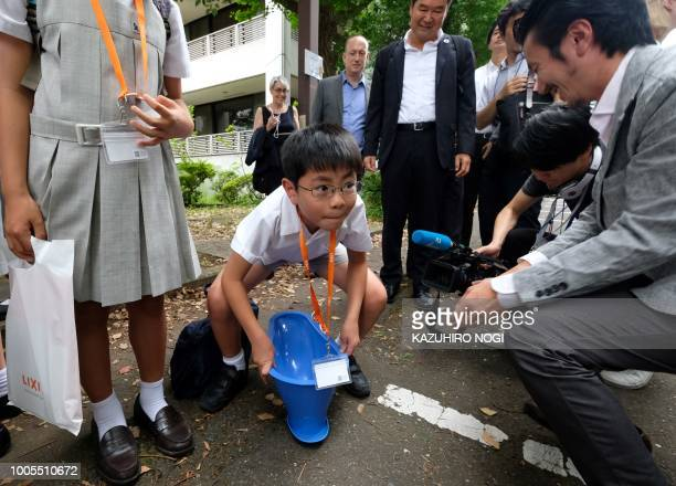 An elementary school student lifts a SATO toilet system made by Japanese household products firm Lixil during a special interactive class with...