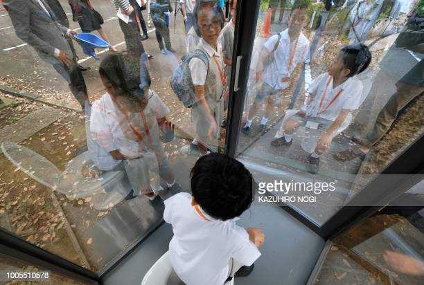 An elementary school student sitting on a toilet in a public display looks outside through oneway glass during a special interactive class with...