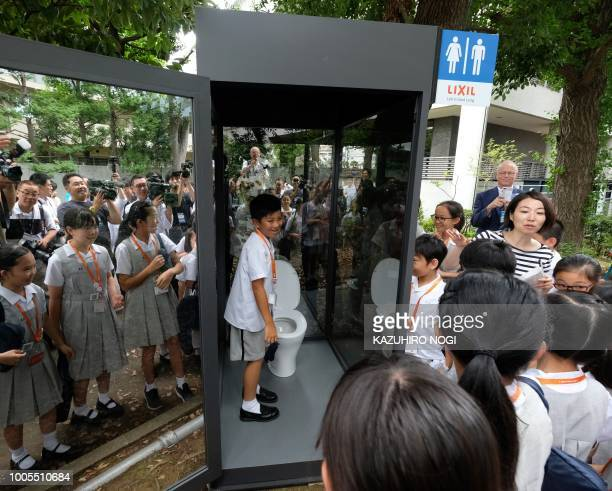 An elementary school student standing inside a public toilet display with oneway glass looks out during a special interactive class with students...