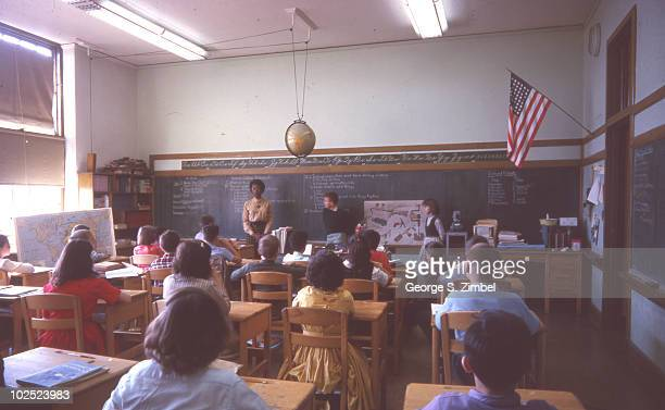 An elementary school student stands at the front of the class, along with the teacher, during a science lesson about machines, Westchester, New York,...