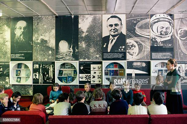 An elementary school teacher stands before her students during a field trip to a rocket science exhibit which contains various display cases and...