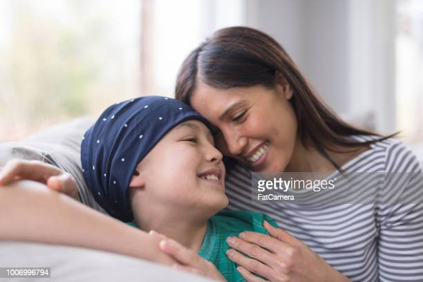 an elementary-age boy battling cancer sits with his mother on the couch - cancer illness stock pictures, royalty-free photos & images