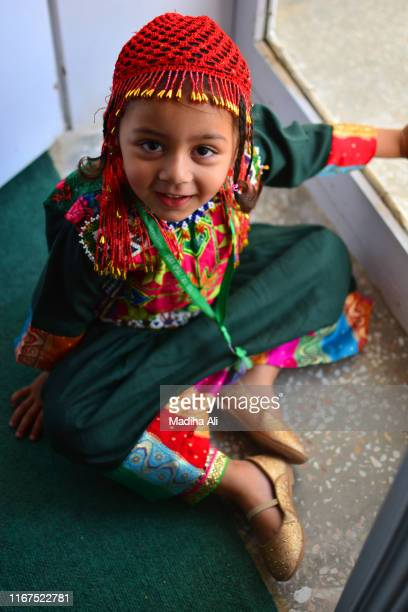 an elemntary aged female / girl wearing traditional kashmiri / afghan clothes, with traditional jewelry and head scarf, which is part of their culture. - pathan girls stock photos and pictures