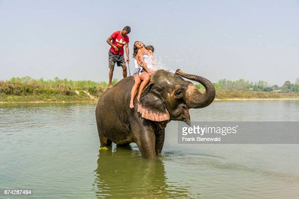 An elephant is splashing water on two tourist women in the Rapti River in Chitwan National Park.