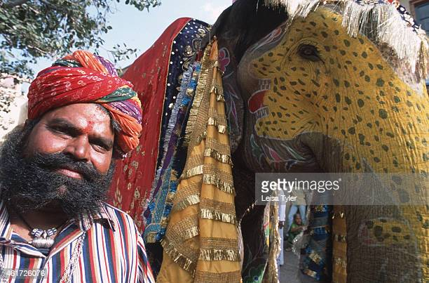 An elephant trainer and his decorated steed wait to take part in the ceremony for the featival of Ganguar a procession leading from the City palace...