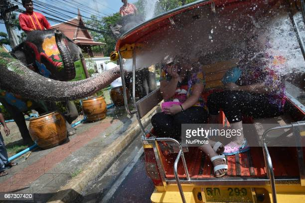 An elephants sprays water on tourist during an event ahead of Songkran festival at an elephant park in Ayutthaya Thailand on April 11 2017