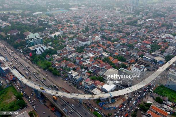 An elevated track for the Jakarta Mass Rapid Transit stands under construction as vehicles travel along a highway in this aerial photograph taken in...